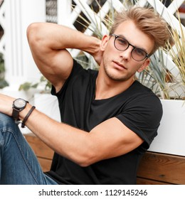 Beautiful model hipster man with sunglasses with a hairstyle in a black T-shirt on the beach near a wooden fence