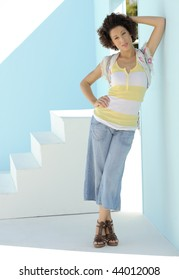 Beautiful model leaning against blue wall on sunny day.