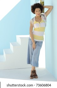 Beautiful model leaning against blue wall in front of stairs on sunny day.