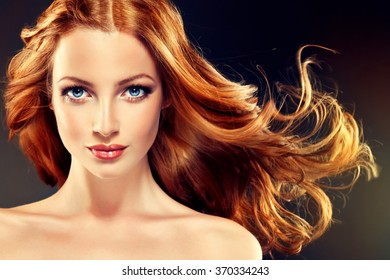 Beautiful model with long curly red hair .  Styling hairstyles curls .Wavy shiny