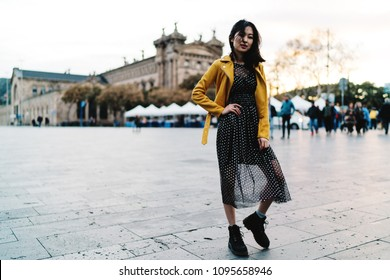Beautiful model look asian woman in stylish outfit posing on a camera while standing on a center city square. Fashion blogger from Asia exploring the city while having free time during business trip