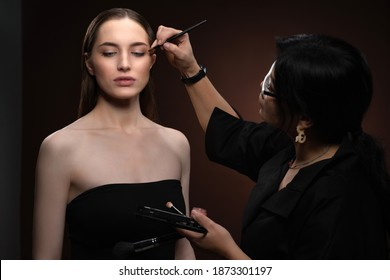 Beautiful model at MUAH artist. Beauty makeup artist working on a fashion model face isolated on black background. Make-up artist, applying eye shadow to the model.
