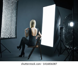Beautiful model on fashion shoot in photo studio with lighting equipment. backstage equipment workplace photo studio concept. Photography of fashion look.