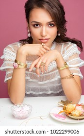 Beautiful model posing with jewelry, cakes and sweets