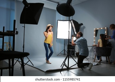 Beautiful model posing for professional photographer in studio
