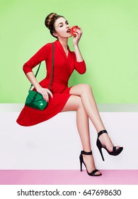 Beautiful model with red dress, black heels shoes and green purse, holding red apple. Isolated on pastel color background.