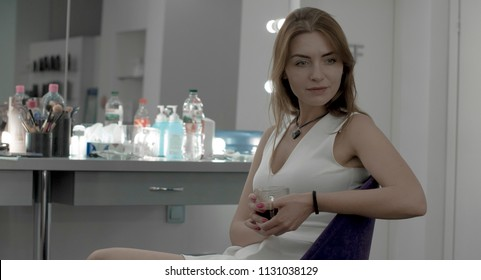 Beautiful model relaxing in makeup room with coffee
