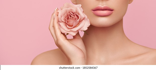 Beautiful model with a rose. Perfect woman face makeup close up. Lipstick. Beautiful nails. Nice smile. Perfect skin