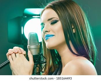 Beautiful Model Sensual singing into a microphone. Long hair, young woman.