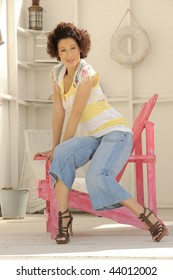 Beautiful model sitting on pink chair in beach house.