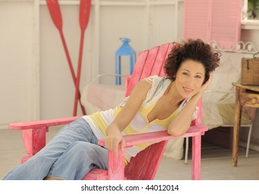 Beautiful model sitting on pink chair in beach house horizontal.
