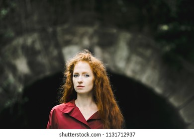 The beautiful model stands near  arch in the park