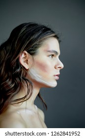 Beautiful model. Stands in profile, makeup with paint strokes on the face. Creative person. Collarbones