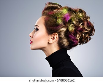 Beautiful model with a stylish hairstyle. Profile portrait of a Fashion model with multicolor hair - posing at studio