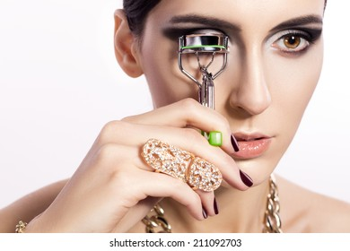 Beautiful model taking eyelash curler in her hand smoky eyes make up and golden ring