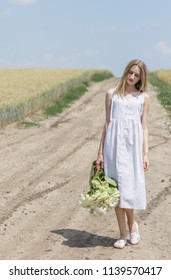 Beautiful model, thin girl blonde on the road in the middle of the field in a white dress with a backpack in her hands. Advertising, cover, photo, beauty