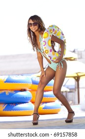 Beautiful model in turquoise swimsuit, with multicolored inflatable ring