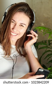 Beautiful model using earphones and holding smartphone while smiling at camera.
