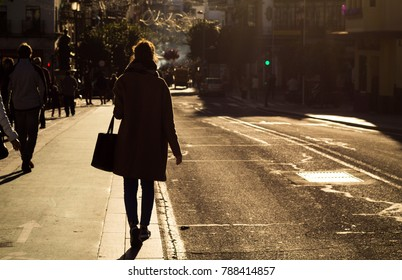 A beautiful model walking in Triana, Seville, a beautiful city in Spain. During the rush hour, golden lights and beautiful silhouettes can be photographed