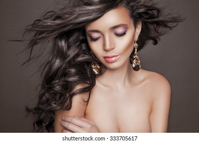 Beautiful model with wavy hairstyle.Portrait of young woman with makeup and clean skin. Toned in warm colors. Studio shot, horizontal