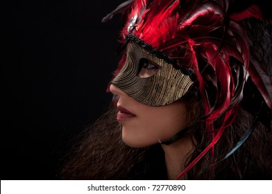 Beautiful model wearing a red feather mask symbolizing mardi gras or venetian carnival over black background