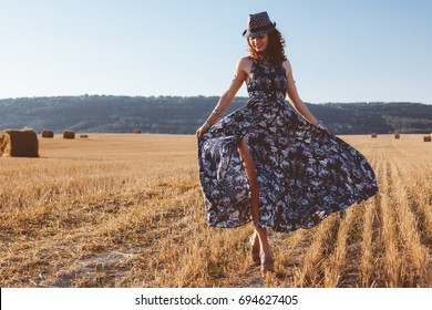 Beautiful model wearing summer cotton maxi dress posing in autumn field with hay stack. Boho style clothing and jewelry.
