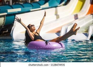 beautiful model wearing sunglasses in black bikini on the inflatable ring in the swimming pool. Summer Vacation. Enjoying suntan. Weekend on resort