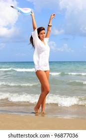 Beautiful model in white shirt posing on the beach