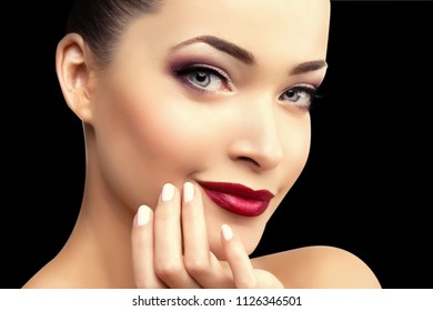 Beautiful model woman on a black background in beauty salon makeup Young modern girl in luxurious spa Lady make up Mascara for long lashes lipstick on lips eye shadow shiny hair manicure with nail
