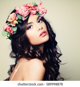 Beautiful Model Woman with Perfect Makeup, Long Curly Hair and Wreath of Flowers