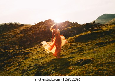 Beautiful model woman run in fashion dress on nature background in sunlight. Concept of Art, Travel, Bohemian Style, Freedom or Scenic Life. Velika Planina or Big Pasture Plateau, Slovenia, Europe.