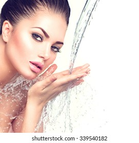 Beautiful Model Woman with splashes of water in her hands. Beautiful Smiling girl under splash of water with fresh skin over blue background. Skin care Cleansing and moisturizing concept. Beauty face
