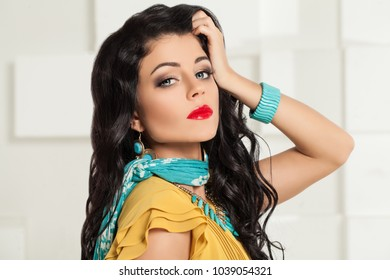 Beautiful Model Woman touching her Hand her Hair. Makeup, Wavy Hair and Blue Female Jewelry