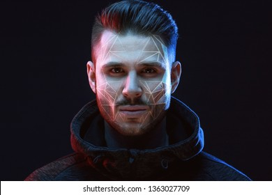 Beautiful model young man with beard on dark background. Face recognition. Biometric verification. The concept of new face recognition technology on a polygonal mesh. Face ID.
