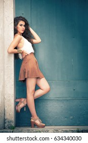 Beautiful model young woman leaning against the wall. Fashionable clothing, curly hair. Posing outdoors. The curly girl wears a white sleeveless shirt, short brown skirt and shoes with heel.