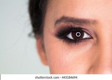 Beautiful model's eyes looking into the camera on a background