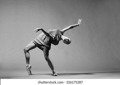 Beautiful modern ballet dancer on tiptoe posing in studio. Extreme flexibility.