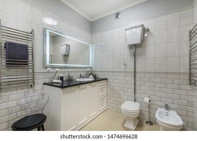Beautiful modern bathroom with large backlit illuminated mirror