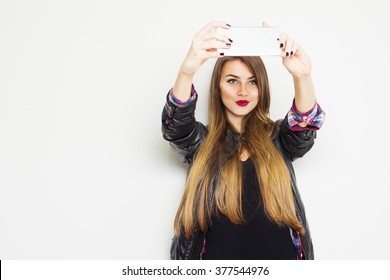 Beautiful modern blonde teenage girl in black leather jacket smiling, taking a selfie on smartphone. Cute young woman photographing herself using cellphone. Horizontal, copy space.