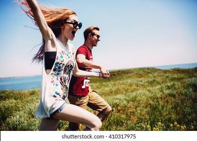 Beautiful modern couple have fun in summer field