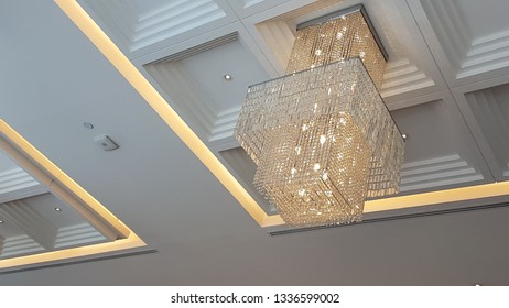 Beautiful modern crystal chandelier hanging on the ceiling of a luxurious room.