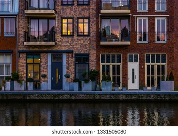 beautiful modern dutch city architecture at night, terraced houses at the canal with balconies, Alphen aan den Rijn, The Netherlands