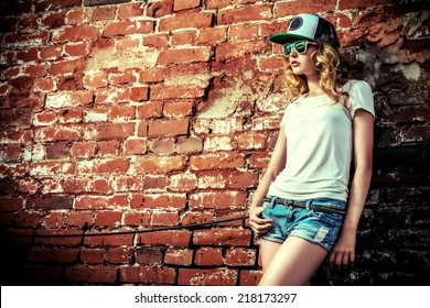 Beautiful modern girl near the brickwall. Youth style. Fashion shot.