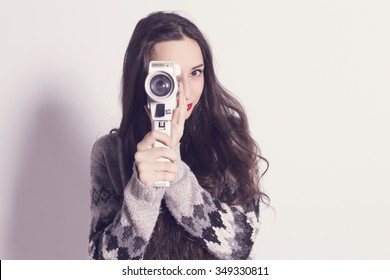 Beautiful modern girl with a very old and dirty super 8mm camera.