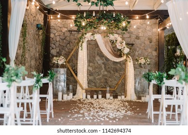 Beautiful modern hexagon wedding arch for unique contemporary wedding ceremony with fresh greenery and lights and candles.