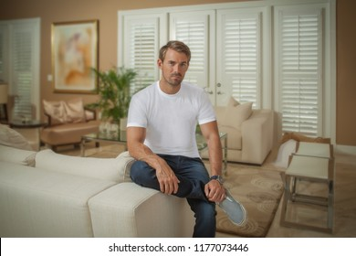 In a beautiful modern living room, the homeowner sits on the edge of the couch arm. He casually looks at the camera as the full view of the room is captured.