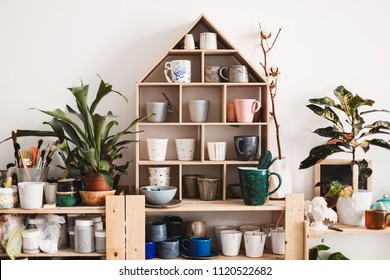 Beautiful modern shelves with colorful handmade subjects at pottery studio. Interior of cozy pottery workshop