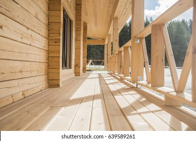 Beautiful modern terrace lounge with pergola and wood fence against sunny forest and blue sky background. eco house made from natural material