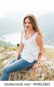 Beautiful modern woman with long hair in a white shirt and blue jeans  outdoors. Smiling girl enjoys fine warm spring weather highly in mountains against the sea.