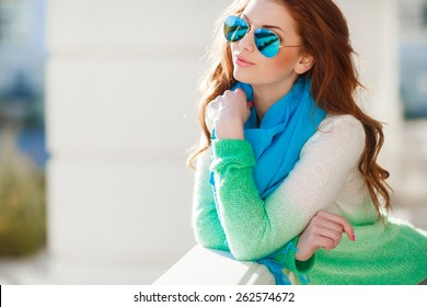 Beautiful modern woman with long red hair in a green-blue sweater and scarf outdoors. Woman with blue sunglasses. Smiling girl